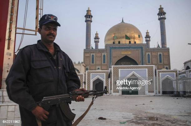 Pakistani policeman stands alert at the shrine a day after a suicide attack at the 13th century old shrine of a Muslim saint in the town of Sehwan in...