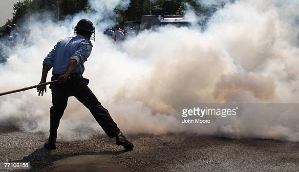 Pakistani policeman stands behind a cloud of tear gas during violent clashes between opposition lawyers and security forces on September 29, 2007 in...