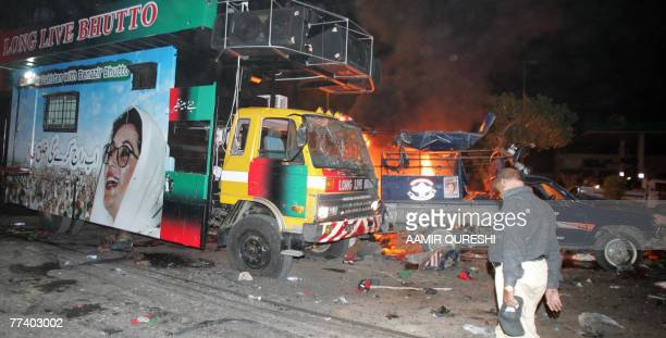 Pakistani policeman stands beside of a burning police van in front of a vehicle carrying of former Pakistani prime minister Benazir Bhutto at the...