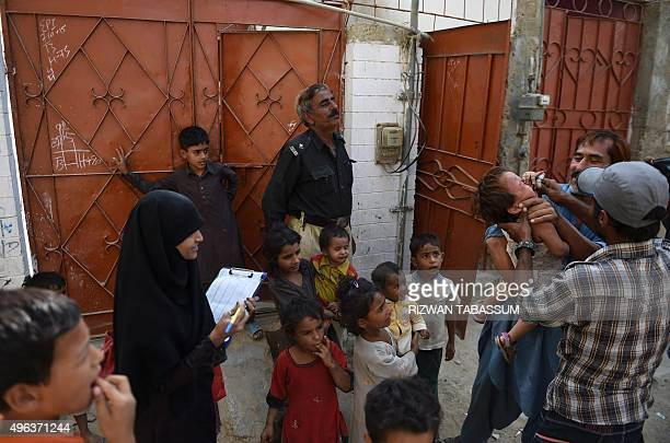 A Pakistani policeman stands guard as a health worker administers polio drops to a girl during a polio vaccination campaign in Karachi on November 9...