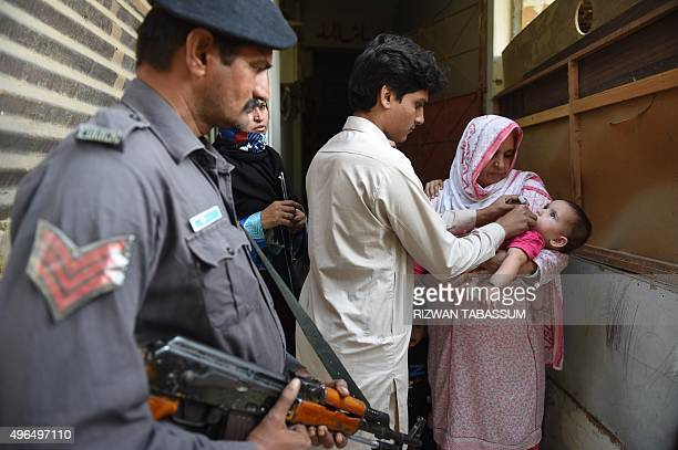 A Pakistani policeman stands guard as a health worker administers polio drops to a child during a polio vaccination campaign in Karachi on November...