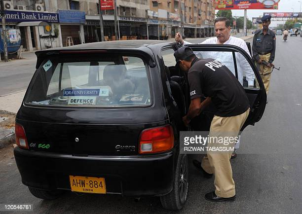 A Pakistani policeman stands guard as another searches a vehicle at a check point on a street in Karachi on August 7 2011 Ethnic and politically...