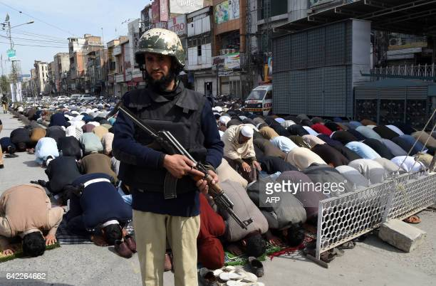 A Pakistani policeman stands guard as Muslim offer Friday prayers on a street in Peshawar on February 17 following bomb attack on a shrine of 13th...