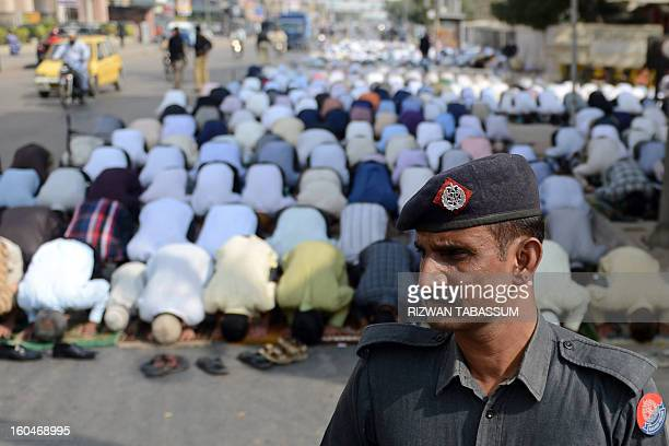 A Pakistani policeman stands guard as Muslims offer Friday prayers in Karachi on February 1 a day after nine people were killed by bombs and...