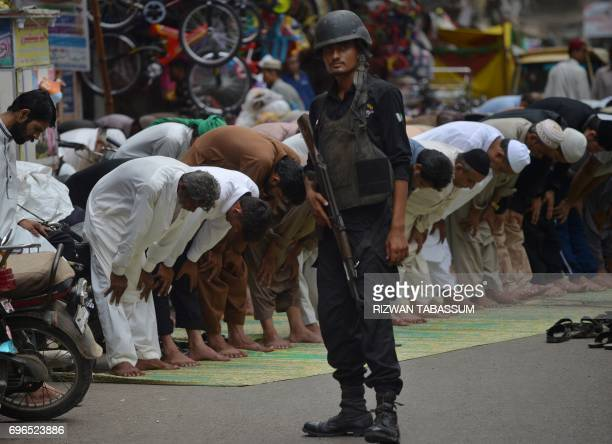 A Pakistani policeman stands guard as resident offer Friday prayers during Ramadan on a street in Karachi on June 16 2017 Muslims throughout the...