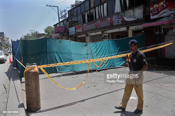 Pakistani policeman stands guard following a bomb blast outside a restaurant in Rawalpindi. A bomb planted on a motorcycle exploded outside a...
