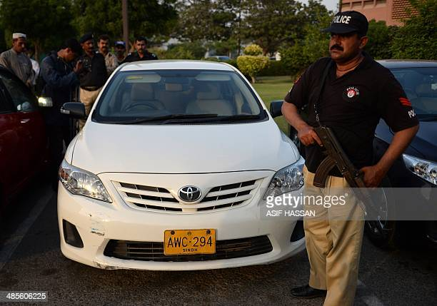 A Pakistani policeman stands guard in front of a car following an attack on prominent Pakistani journalist Hamid Mir in Karachi on April 19 2014...