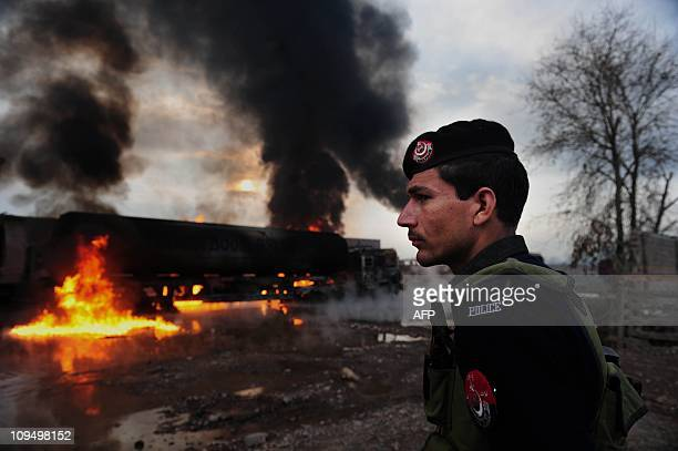 A Pakistani policeman stands guard next to burning NATO oil tankers following an attack at a terminal on the outskirts of Peshawar on February 25...