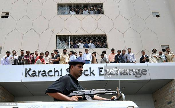 A Pakistani policeman stands guard on a vehicle as angry Pakistani small investors stage a protest outside The Karachi Stock Exchange in Karachi on...