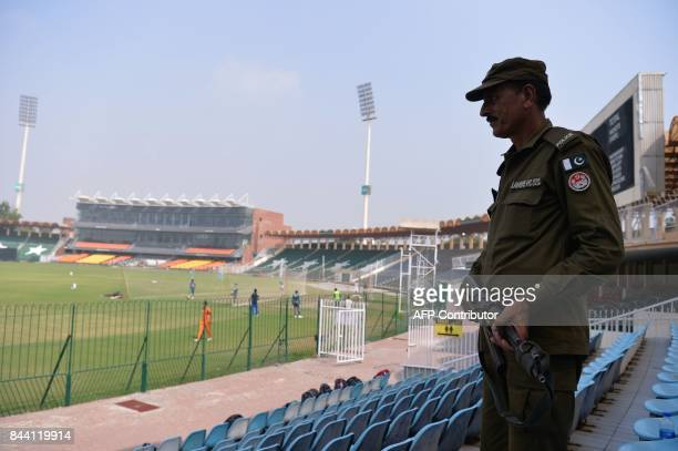 A Pakistani policeman stands guard while national cricket team players take part in a practice session at the Gaddafi Cricket Stadium in Lahore on...
