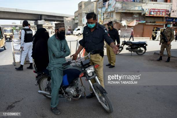 Pakistani policeman stops motorcyclists for pillion riding as a preventive measure against the spread of the COVID-19 coronavirus after a provincial...