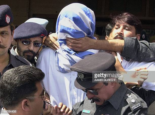 A Pakistani policeman tries to cover the mouth of Britishborn Pakistani militant Sheikh Omar as he tries to shout a message to the press outside a...