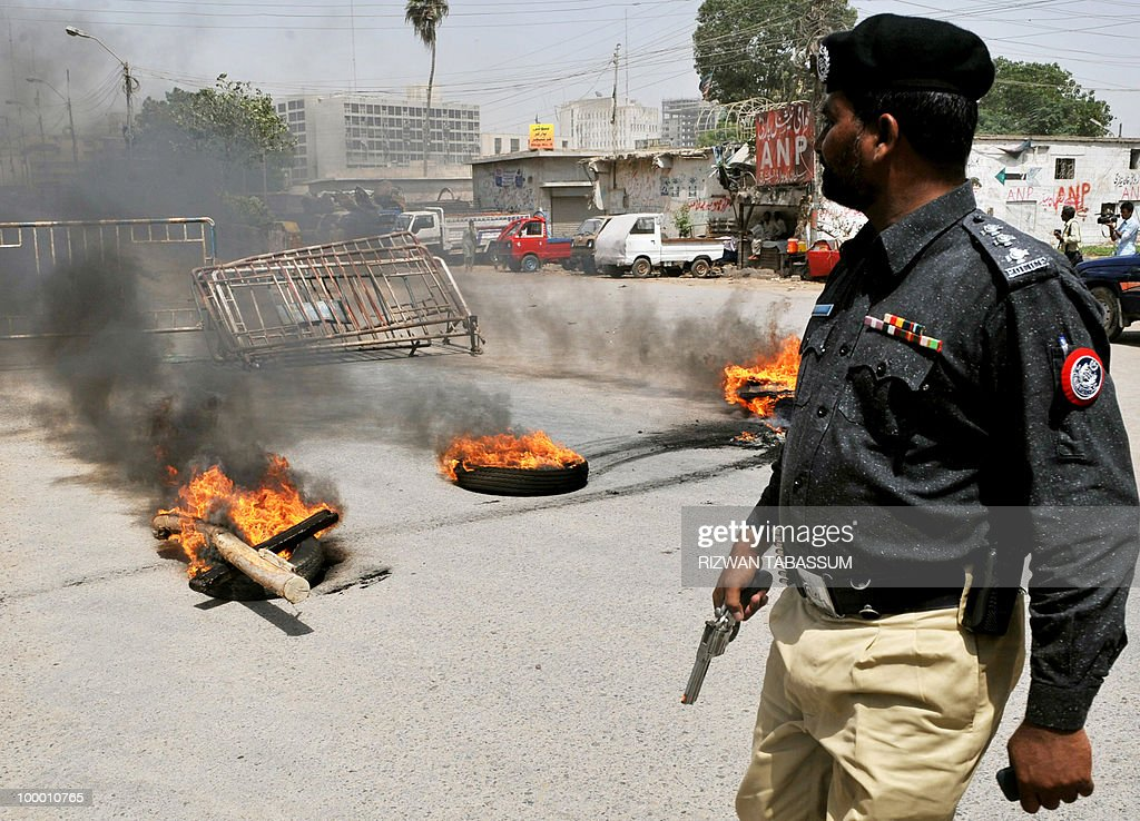 A Pakistani policeman walks past burning tyres torched by an angry mob during a protest against alleged target killings in Karachi on May 20, 2010. At least 17 people including two children have been killed in political clashes in Pakistan's financial capital Karachi in the past two days, a government official and police said. Police and paramilitary have been put on high alert and authorities closed all schools and colleges after the latest outbreak of politically related violence in Karachi, the biggest and richest city in Pakistan.