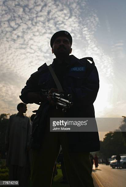 Pakistani policeman watches an antigovernment protest on November 4 2007 in Islamabad Pakistan A small group of demonstrators held signs and chanted...