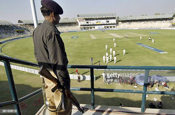 Pakistani policeman watches England cricket team players as they leave the field for lunch during the fourth day of the first Test match in Multan...