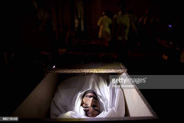 Pakistani policeman's body lays in a casket lit up by a mobile phone flashlight after he was killed in the suicide bomb attack killing at least 23...