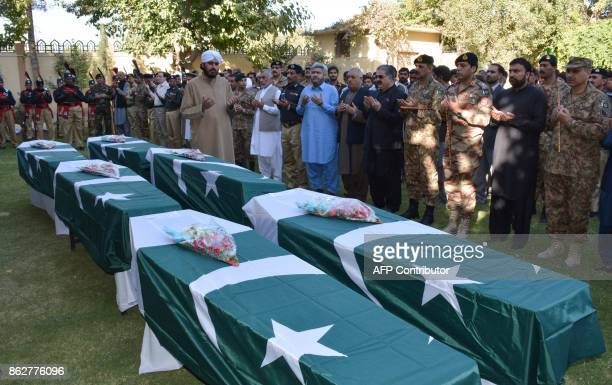 Pakistani policemen and officials pray in front of the coffins of policemen who were killed in a suicide blast during a funeral in Quetta on October...