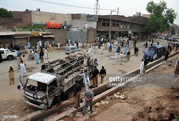 Pakistani policemen and onlookers are seen at the site of an attack in Peshawar on August 11 2011 Bombers killed up to six people in the Pakistani...