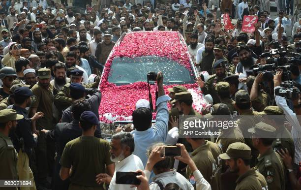 TOPSHOT Pakistani policemen and supporters of the JamaatudDawa organisation gather around the car carrying leader Hafiz Saeed as he arrives at a...