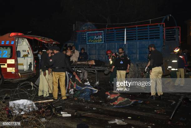 Pakistani policemen and volunteers move the bodies of victims at the site of a bomb explosion in Lahore on February 13 2017 An explosion killed at...