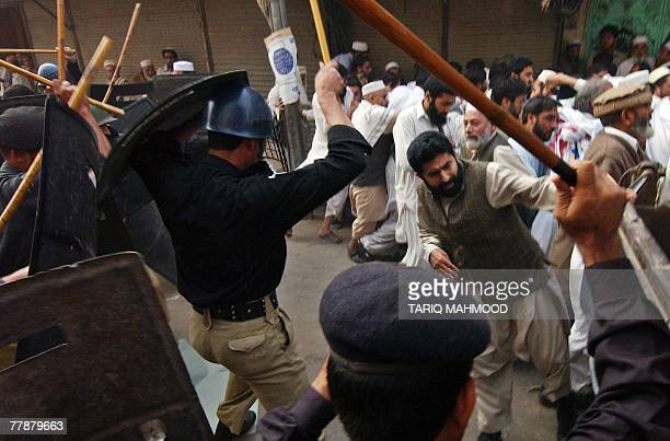 Pakistani policemen beat fundamentalist party JamaatiIslami protesters during an antiMusharraf rally in Peshawar 13 November 2007 Pakistani...