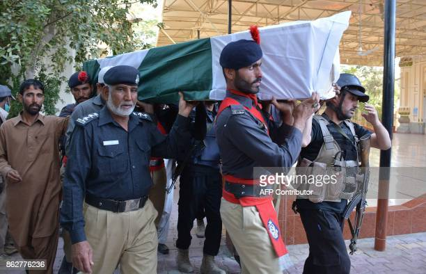 Pakistani policemen carry a coffin of colleague who was killed in suicide blast in Quetta on October 18 2017 At least six people were killed and many...