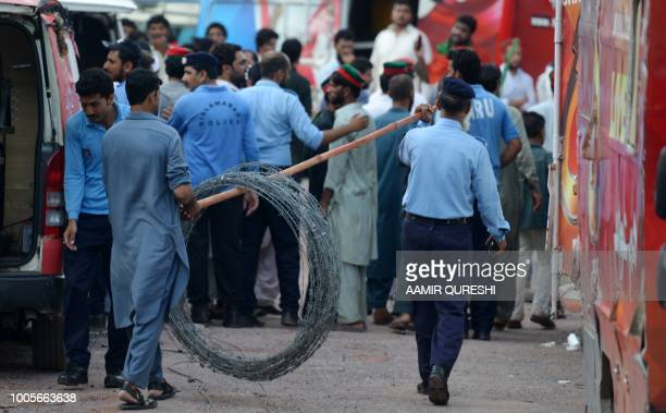 Pakistani policemen carry barbwire to prevent supporters of Pakistan's cricketer-turned politician Imran Khan, and head of the Pakistan...