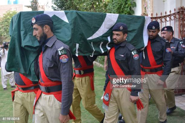 Pakistani policemen carry the coffin of senior police officer Sajid Khan Mohmand who was killed in a bomb explosion earlier in the day during his...