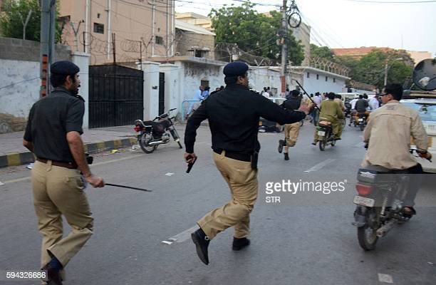 TOPSHOT Pakistani policemen chase activists from the Muttahida Qaumi Movement politicial party during a clash in Karachi on August 22 2016 Activists...