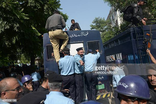 Pakistani policemen climb on top of a prison van carrying arrested opposition workers as they leave the court area following a protest in Islamabad...