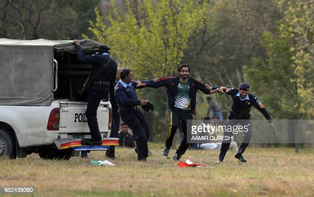 Pakistani policemen detain a kite flyer at a park in Islamabad on March 12 during the Basant Kite Festival which is traditionally celebrated in...
