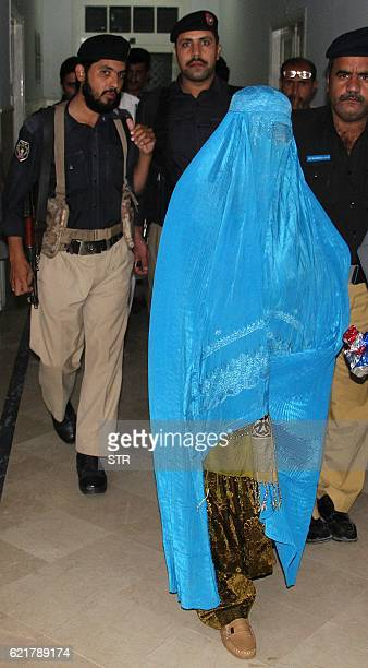 Pakistani policemen escort Afghan refugee woman Sharbat Gula as she leaves the Lady Reading Hospital where she was treated in Peshawar on November 9...