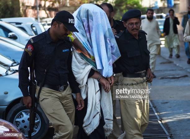 Pakistani policemen escort an arrested founding member of an ethnic Pashtun movement Alamzeb Mehsud at a court in Karachi on January 22 2019...