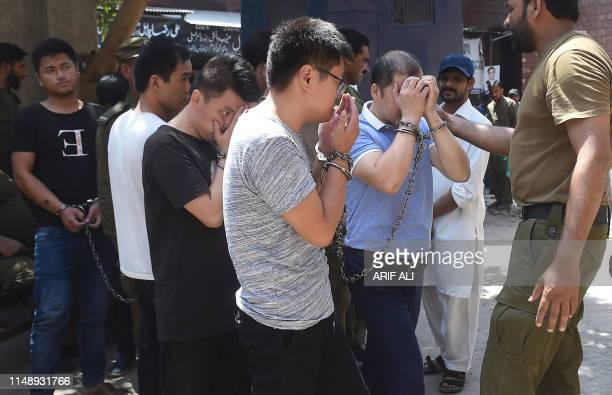 Pakistani policemen escort handcuffed Chinese nationals accused for allegedly luring young Pakistani girls into fake marriages and forcing them into...