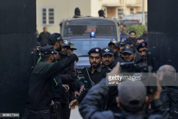 Pakistani policemen escort the police van carrying a suspect accused of raping and murdering a young girl as they leave an antiterrorist court in...