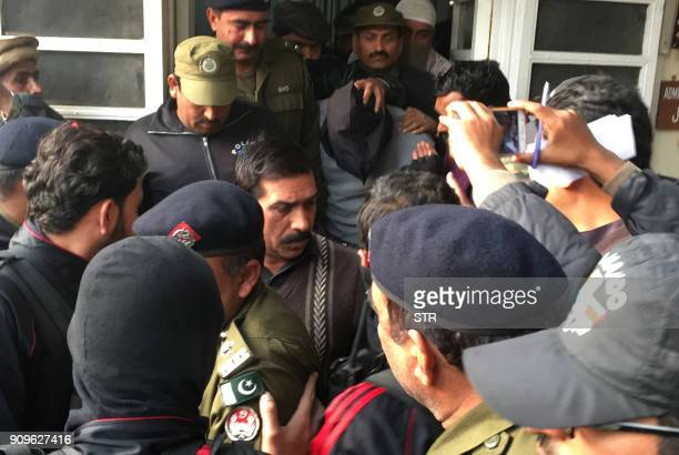 Pakistani policemen escort the suspect accused of raping and murdering a young girl as they leave an antiterrorist court in Lahore on January 24 2018...