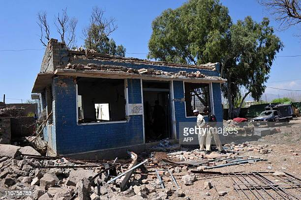 Pakistani policemen examine a damaged police station following a suicide car bomb attack in Hangu district on March 24 2011 A suicide car bomb...