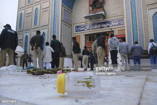 Pakistani policemen gather at the site a day after it was hit by suicide attack at the 13th century old shrine of a Muslim saint in the town of...