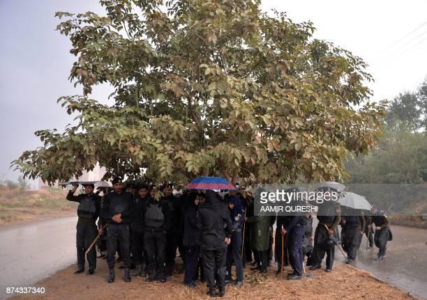 Pakistani policemen gather under a tree during heavy rain near an accountability court where ousted Pakistani prime minister Nawaz Sharif appear...