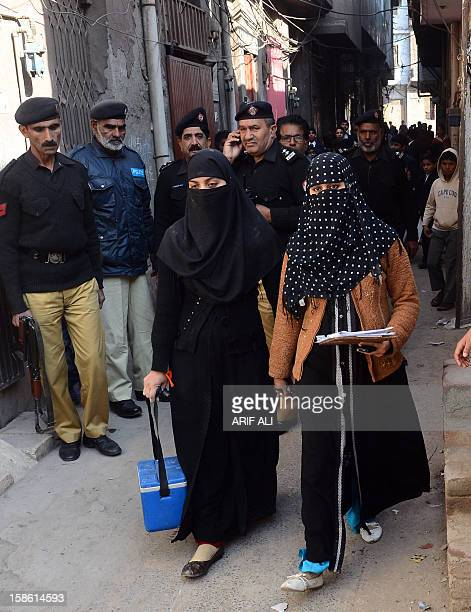 Pakistani policemen guard polio vaccination workers during a door to door polio campaign in Lahore on December 21 2012 This week nine people working...