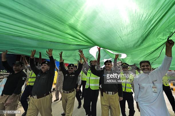 Pakistani policemen hold a giant national flag celebrating to mark the country's Independence Day in Peshawar on August 14 2018 Pakistan celebrates...