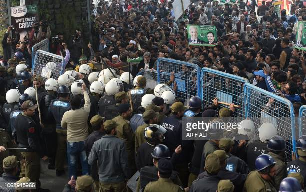 TOPSHOT Pakistani policemen hold supporters of arrested opposition leader Shahbaz Sharif outside the corruption court during Sharif case hearing in...