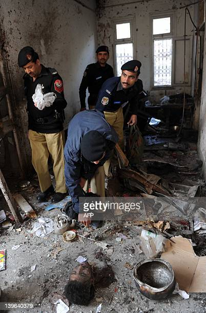 Pakistani policemen inspect a damaged room and the remains of a suicide bomber following a bomb blast at a police station in Peshawar on February 24...