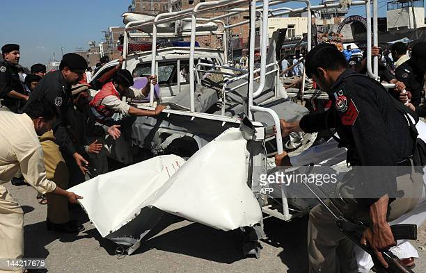 Pakistani policemen remove a badly damaged police vehicle from the road following a bomb explosion in Peshawar on May 12 2012 A remotecontrolled bomb...