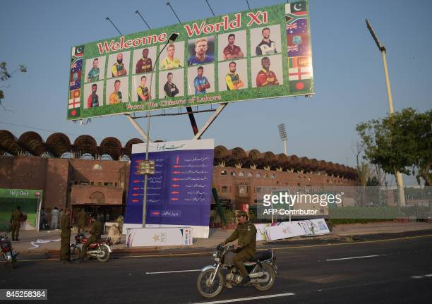 Pakistani policemen ride past a billboard featuring International World XI cricketers displaying outside the Gaddafi Cricket Stadium in Lahore on...