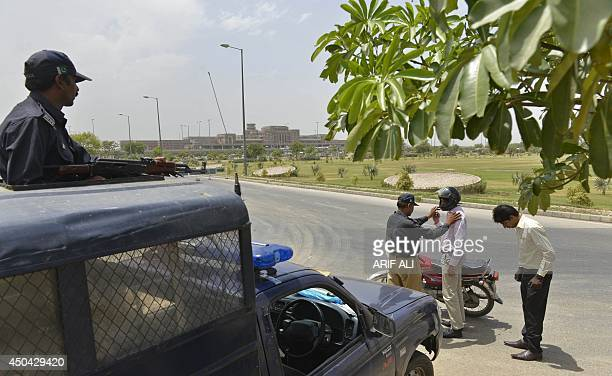 Pakistani policemen search motorcyclist outside the Allama Iqbal International Airport in Lahore on June 11 after security in the country was beefed...