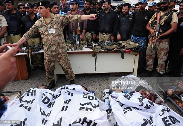 Pakistani policemen show the seized weapons in front of the dead bodies of militants at the Jinnah International Airport in Karachi on June 9 2014...