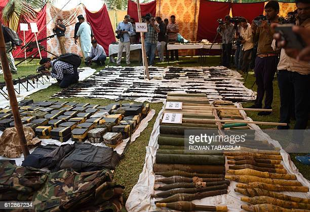 Pakistani policemen stand beside seized weapons displayed for the media in Karachi on October 5 2016 Local media reported that the police raid...