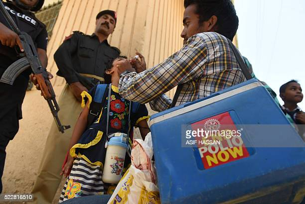 Pakistani policemen stand guard as a health worker administers polio drops to a child during a polio vaccination campaign after a day of an attack by...
