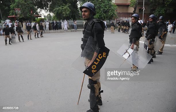 Pakistani policemen stand guard as activists of Pakistani religious party Ahle Sunnat Wal Jamaat take part in an anti Imran Khan and TahirulQadri...